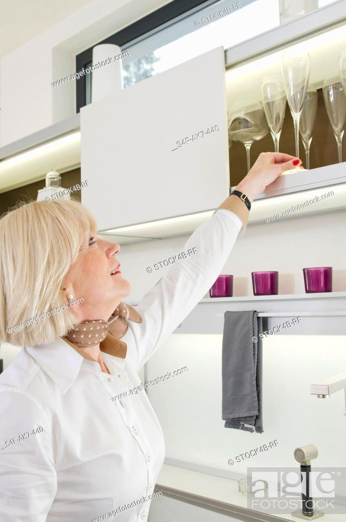 Stock Photo: Senior woman taking champagne glass from kitchen cupboard.