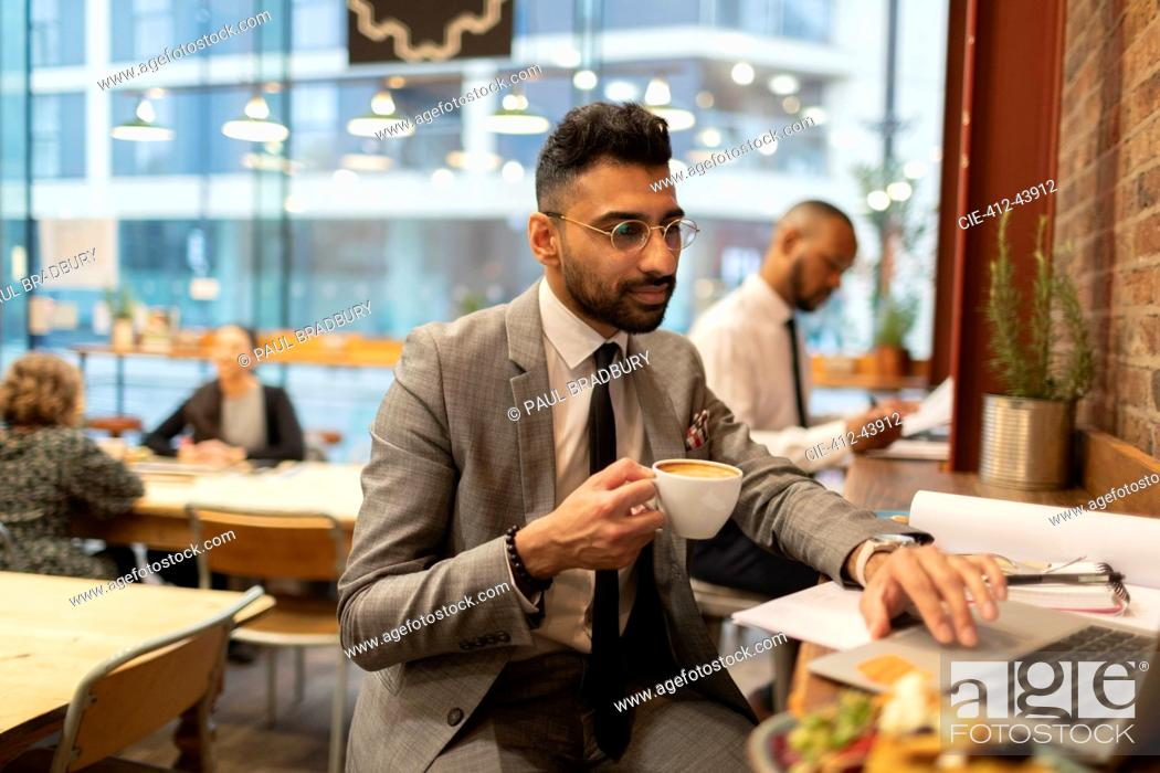 Stock Photo: Focused businessman drinking coffee and working at laptop in cafe.