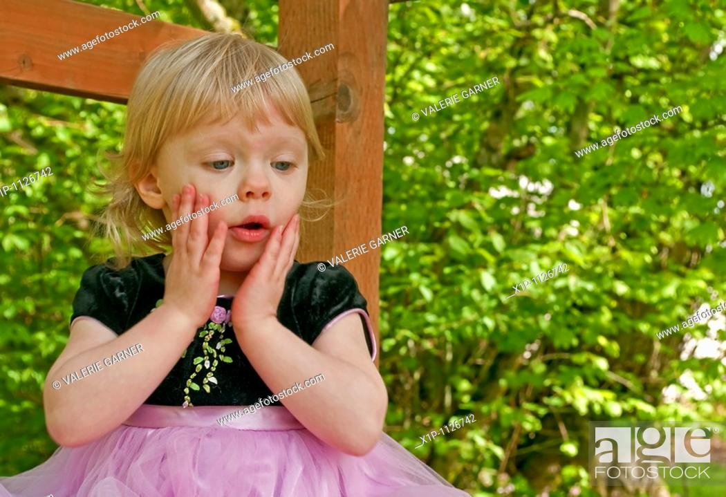 Stock Photo: This stock image shows a two year old toddler girl outdoors in a pink princess dress with a surprised expression on her face Her little hands are on her cheeks.