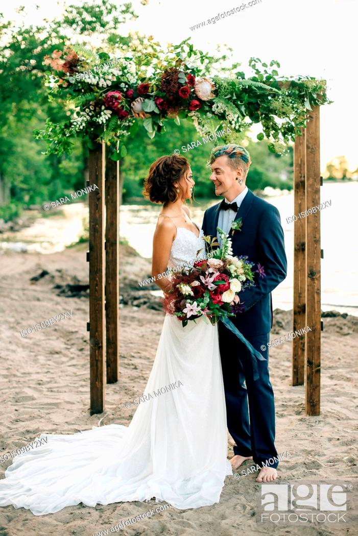Stock Photo: Romantic bride and groom looking at each other on lakeside, Lake Ontario, Toronto, Canada.