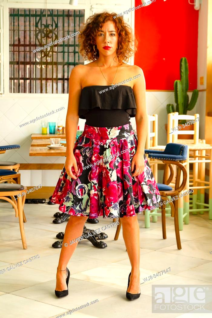 Stock Photo: Vertical whole shot of young woman dressed in a black top and a flower skirt with heels, with the pose and the defiant look forward.