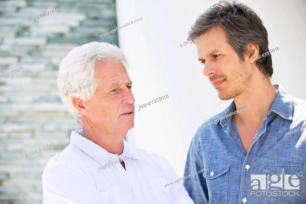 Stock Photo: Mid adult man talking to his father.