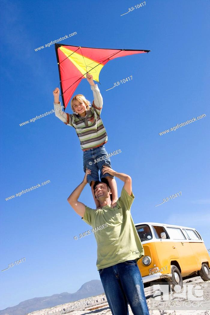 Stock Photo: Boy 6-8 standing on father's shoulders with kite on beach, camper van in background, low angle view.