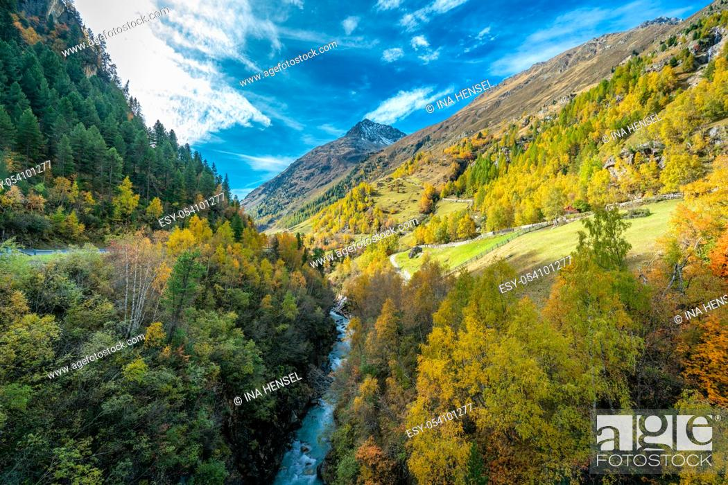 Stock Photo: View to the Wildspitze mountain at the Venter Ache valley near Winterstall with beautiful coloured trees on a bright autumn day with blue skies.