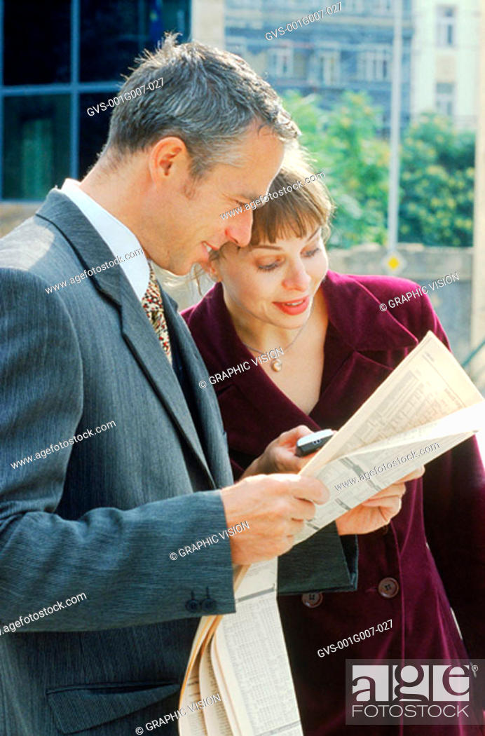 Stock Photo: Young professionals reading the newspaper.