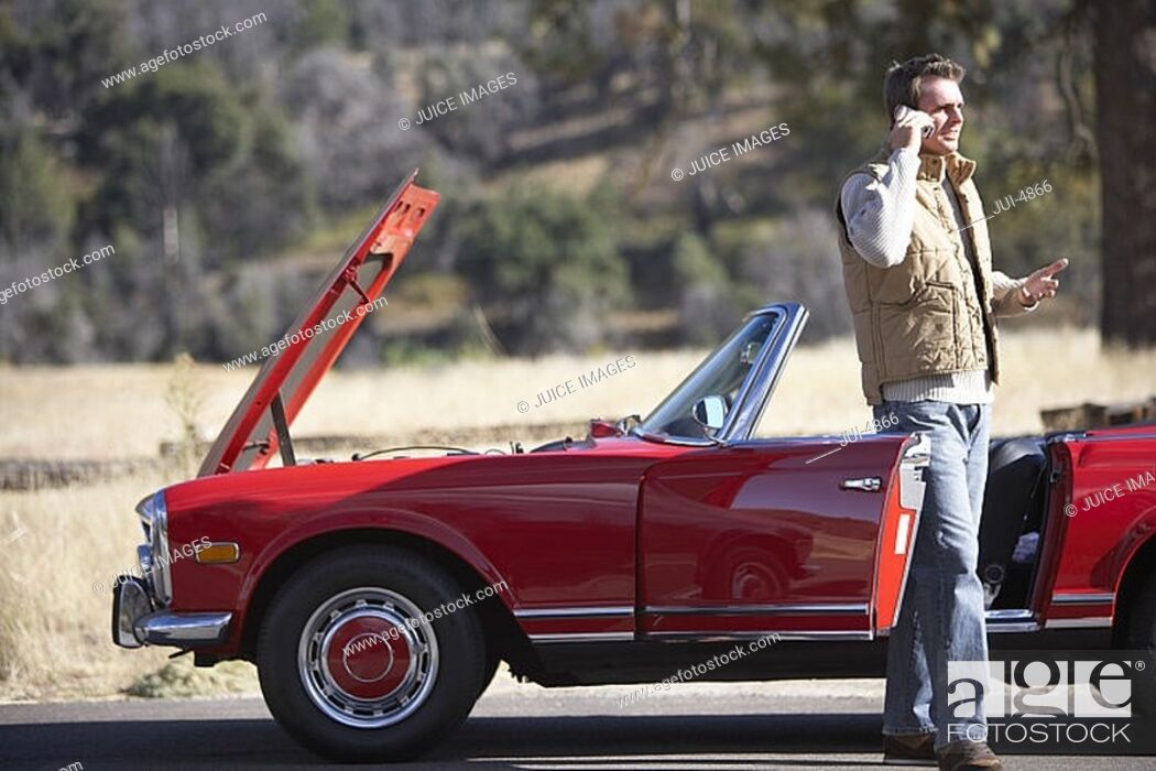 Stock Photo: Man standing at roadside beside red convertible car with engine trouble, using mobile phone.