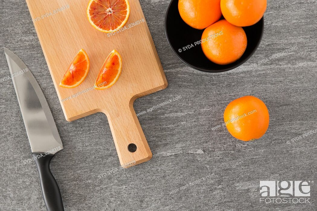 Stock Photo: close up of oranges and knife on cutting board.