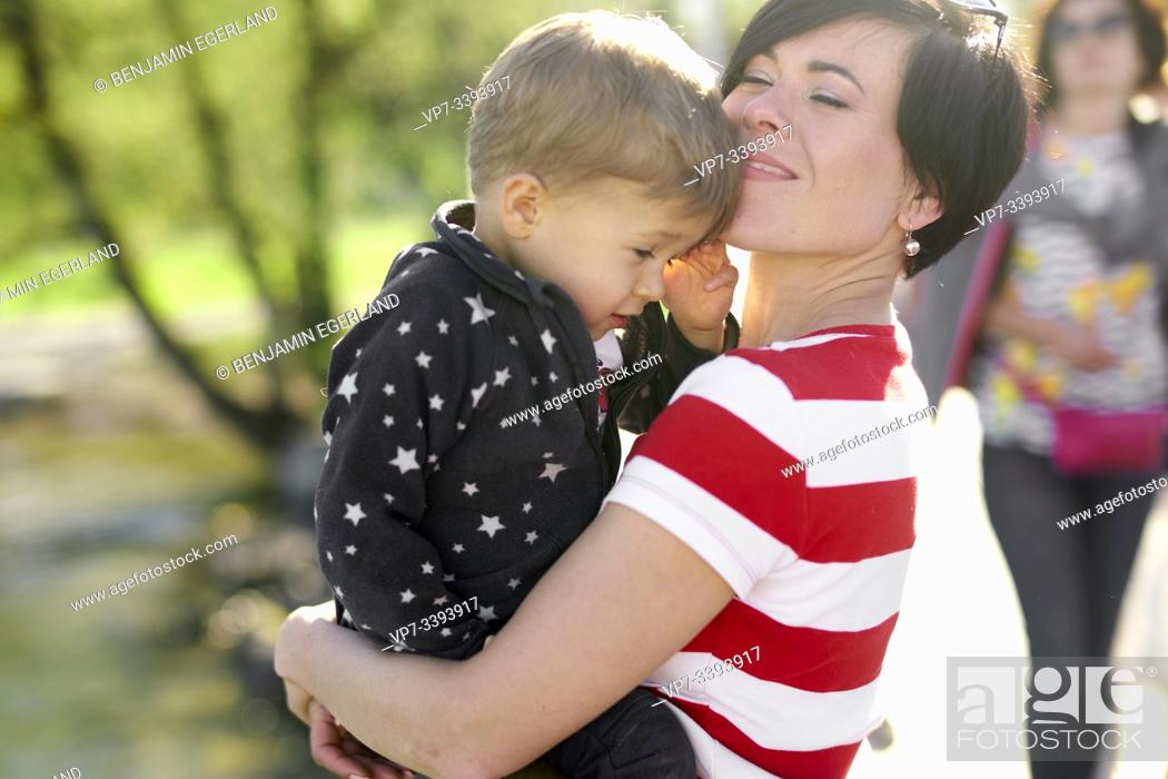 Stock Photo: happy woman enjoying togetherness with son, toddler child, outdoors in park.