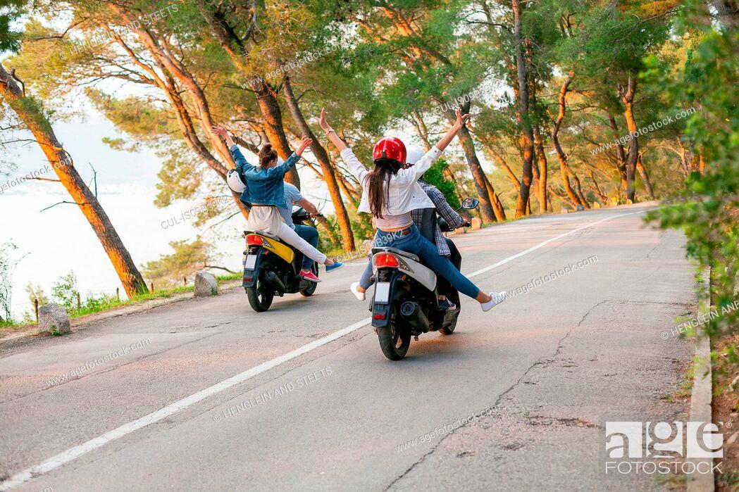 Stock Photo: Rear view of two couples riding mopeds on rural road, Split, Dalmatia, Croatia.