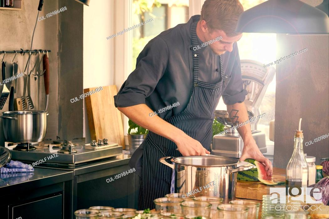 Stock Photo: Chef cooking in commercial kitchen.