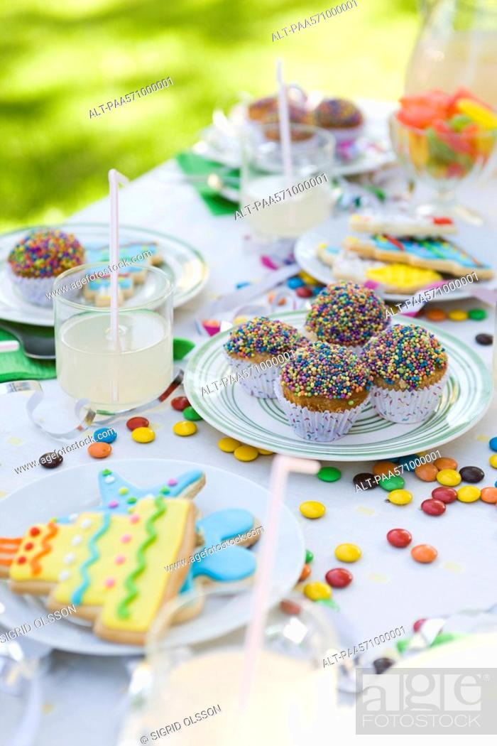 Stock Photo: Iced cookies and cupcakes on table decorated with streamers and candy.