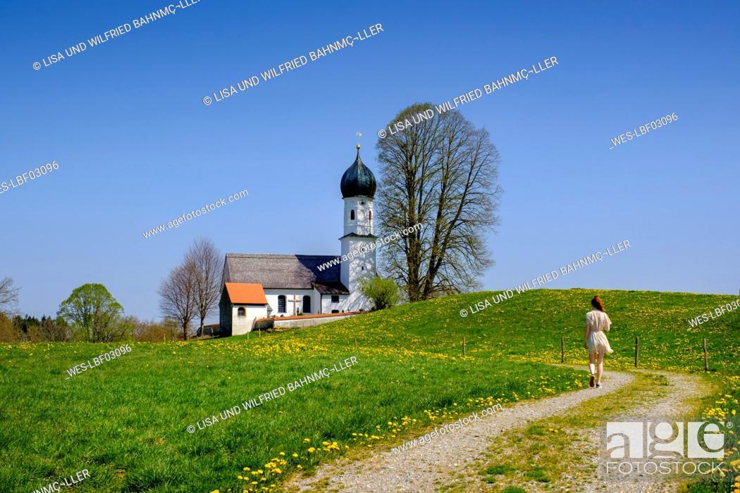 Stock Photo: Germany, Bavaria, Bad Heilbrunn, Teenage girl walking along countryside dirt road toward¶ÿChurch of Saint Mary.