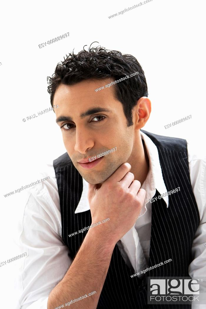 Stock Photo: Handsome male wearing a white shirt and black pinstripe vest and hand under chin, isolated.