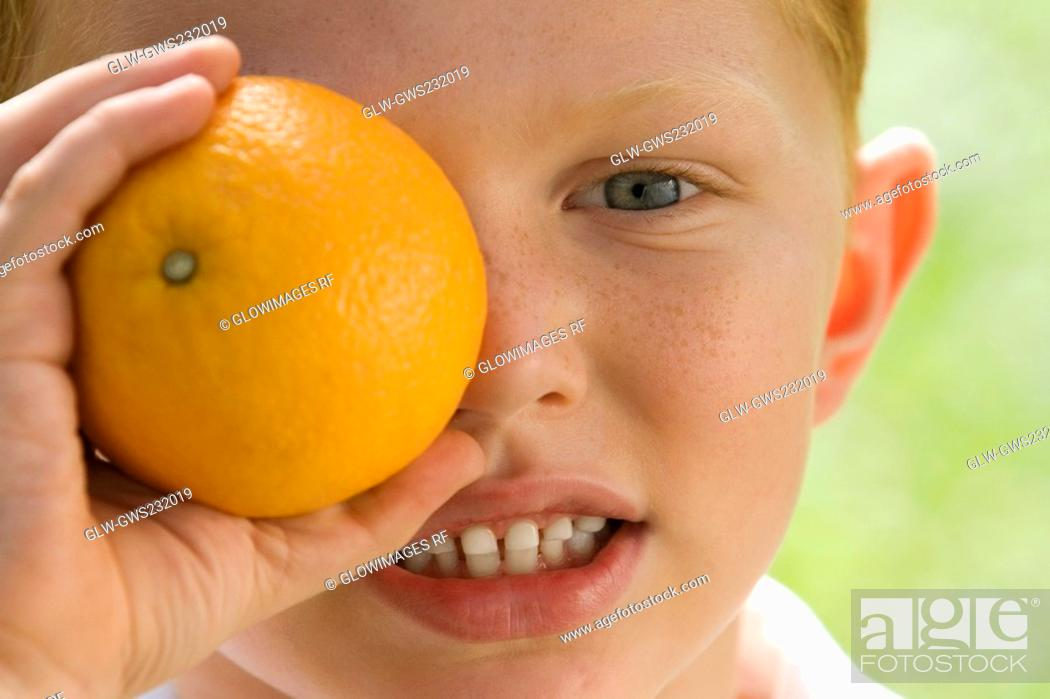Stock Photo: Portrait of a boy holding an orange over his eye.