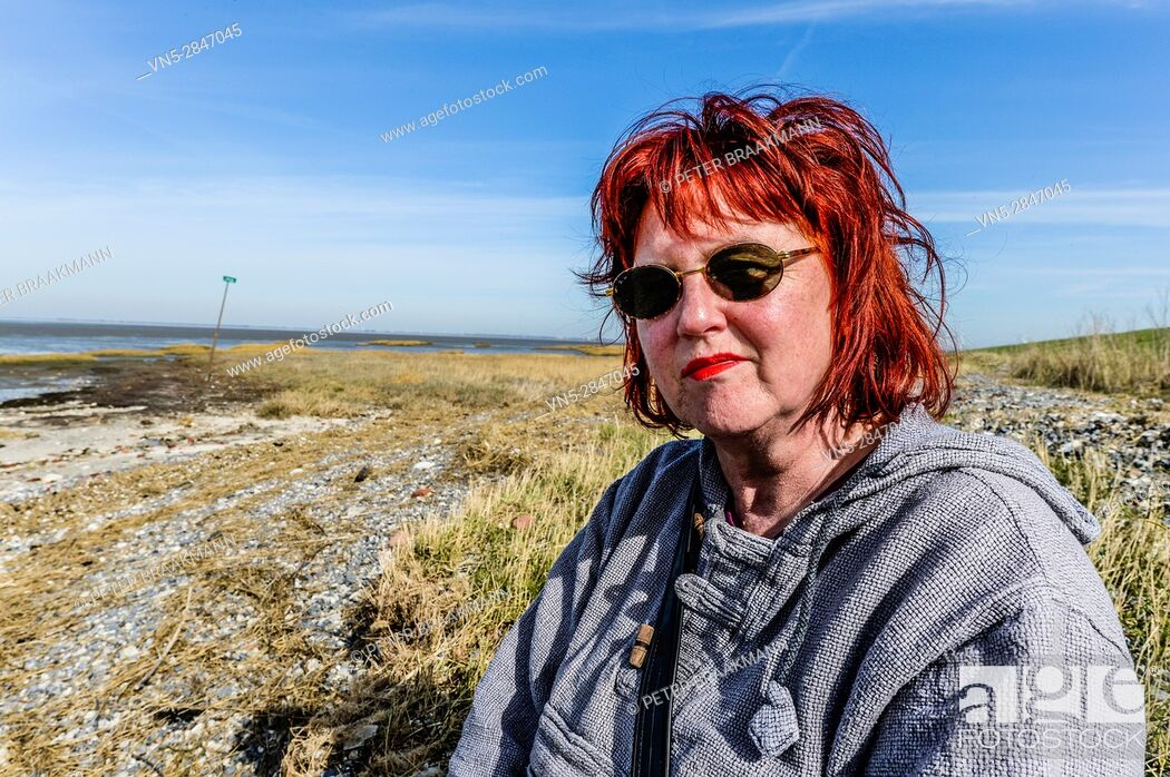 Stock Photo: Krabbendijke The Netherlands - Woman sitting and enjoying the sun with the Oosterschelde in the background.