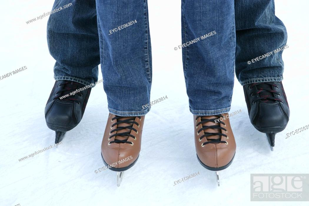 Stock Photo: Two people wearing jeans on ice skates.