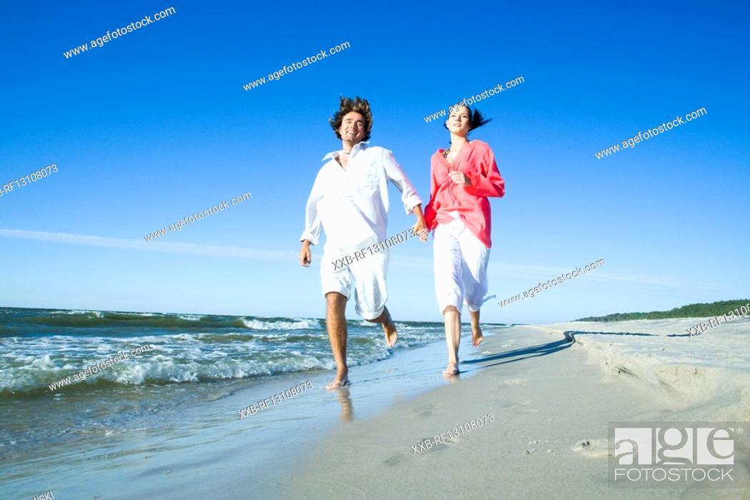 Stock Photo: couple running on seaside.