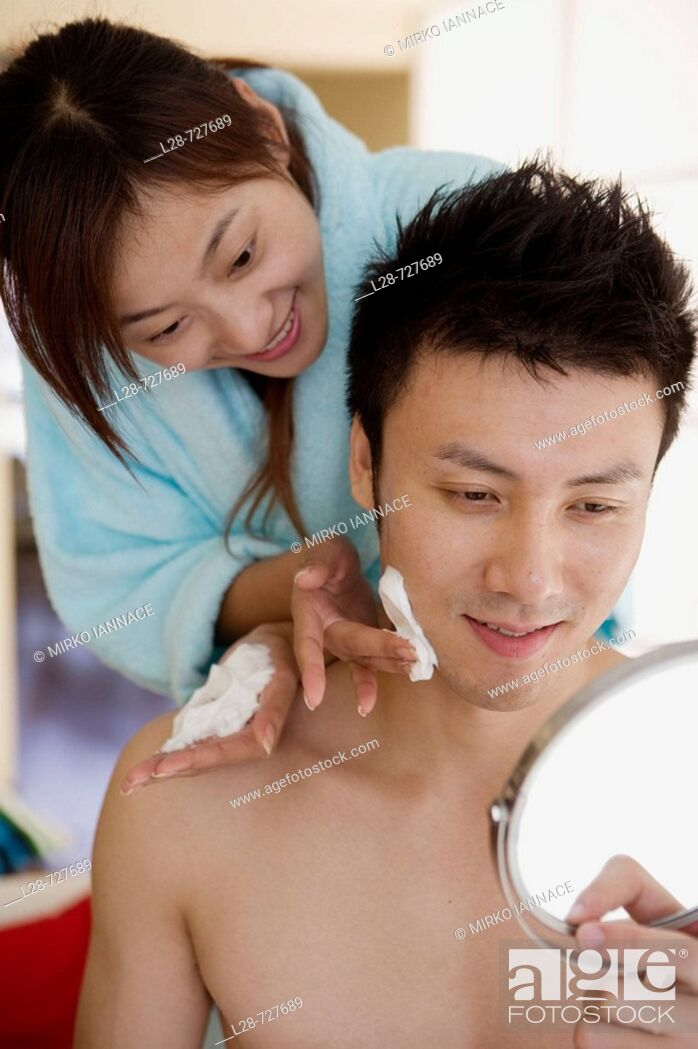 Stock Photo: Young woman shaving young man, smiling, close-up.