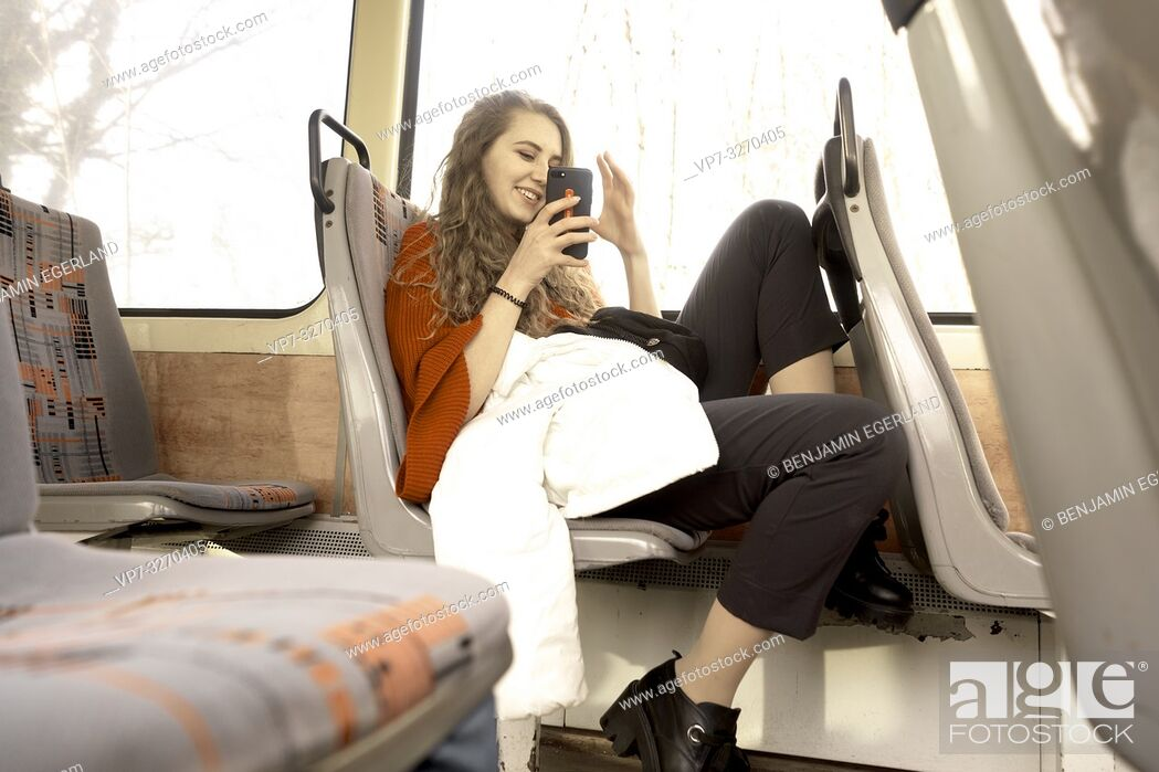 Stock Photo: young woman sitting in public transport, using phone, in city Cottbus, Brandenburg, Germany.