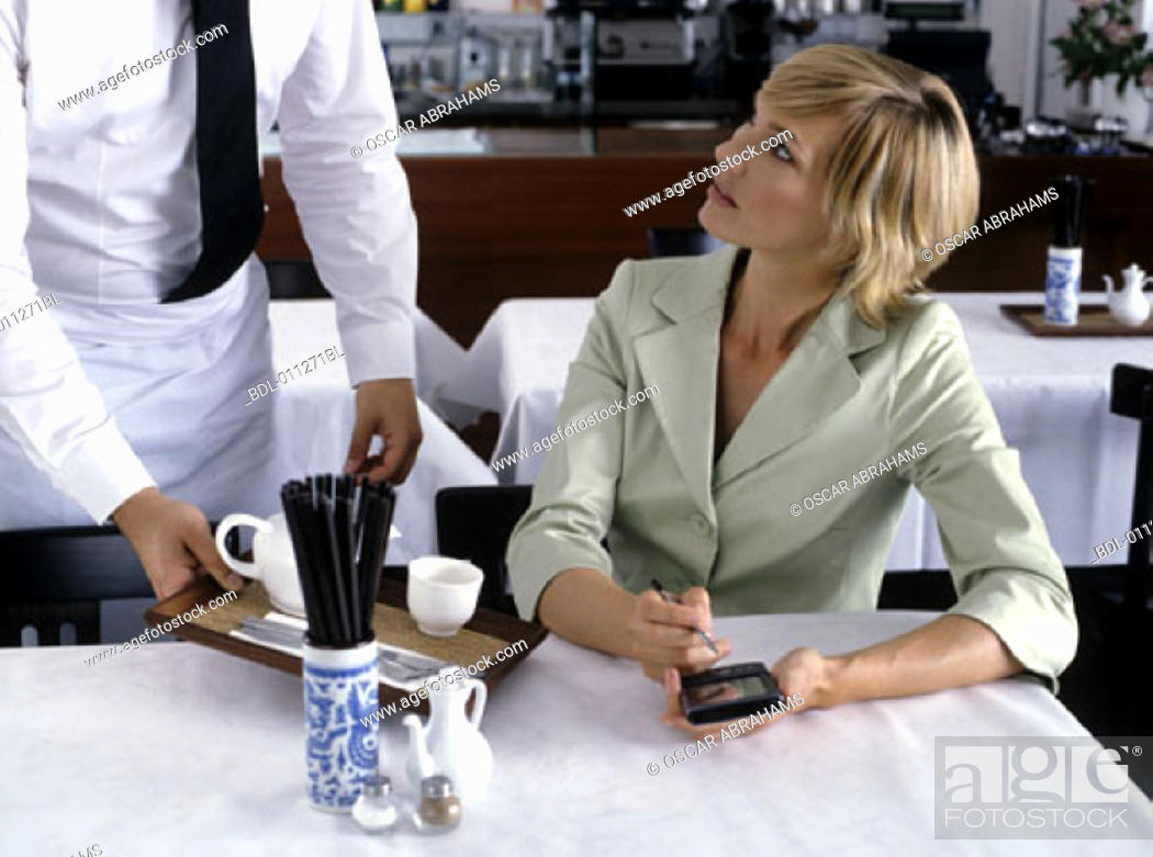 Stock Photo: woman working with electronic organizer while being served in restaurant.