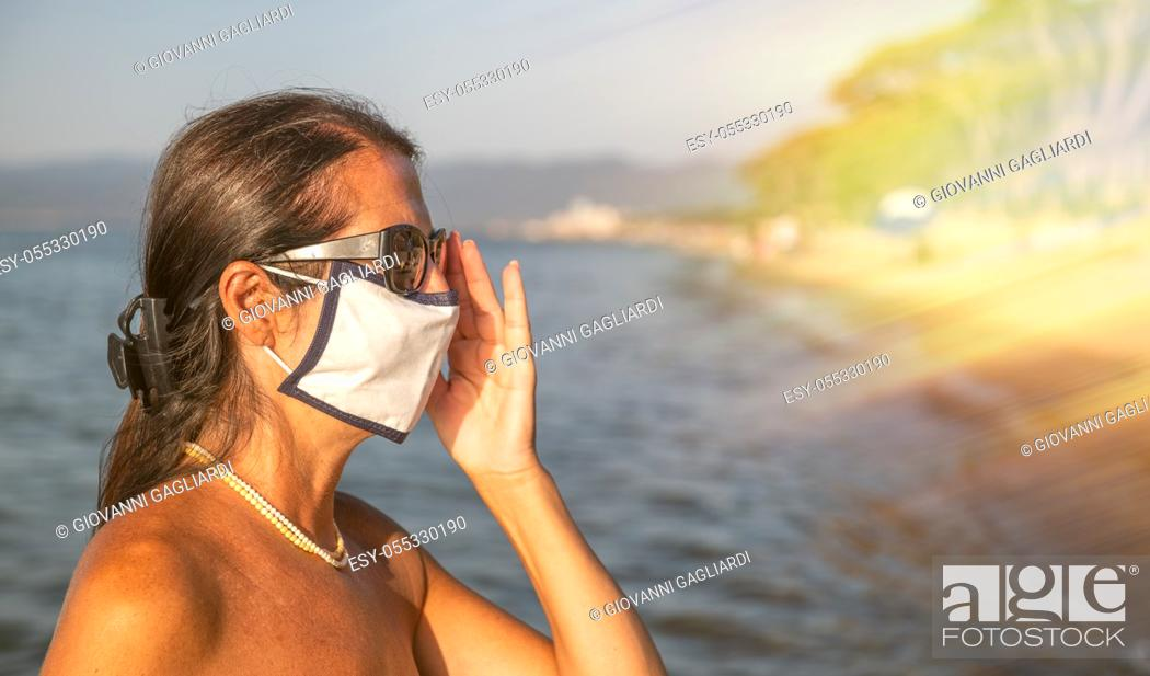 Photo de stock: Woman walking on the beach wearing mask in coronavirus times.