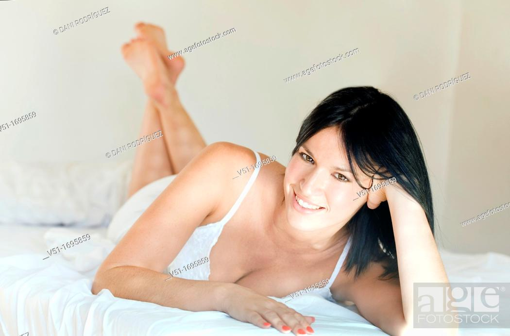 Stock Photo: Portrait of a pretty brunette woman smiling at camera in bed.