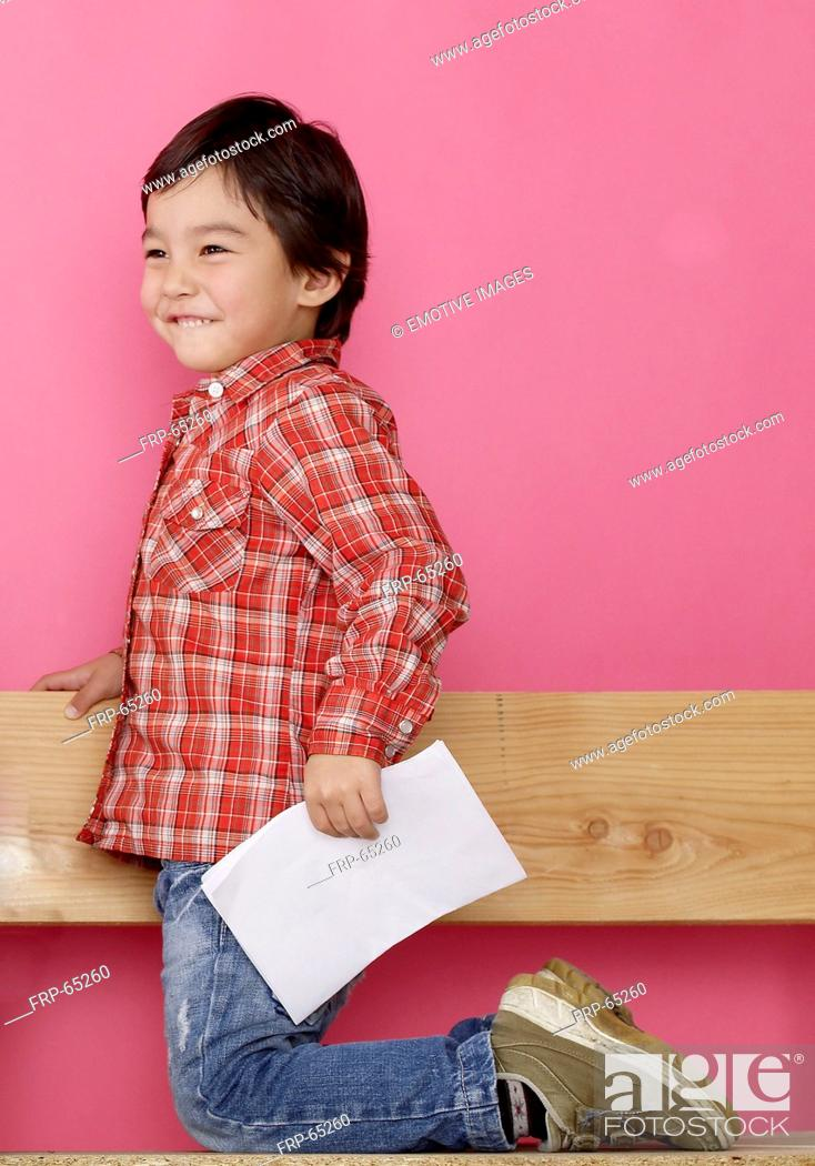 Stock Photo: Asian boy on a bench.