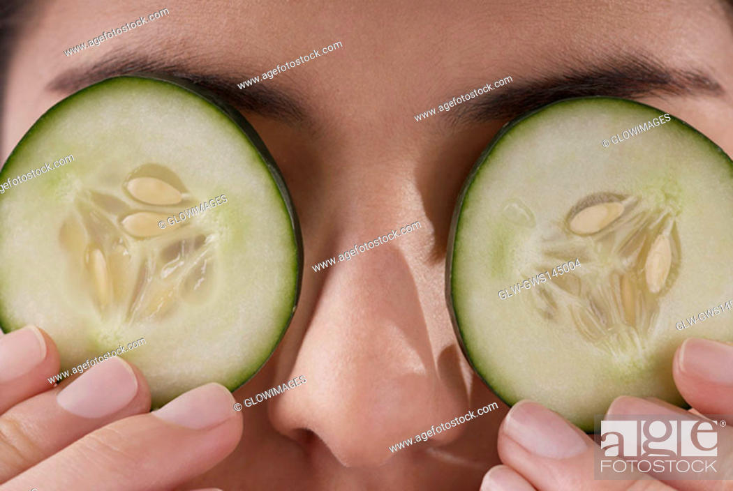 Stock Photo: Close-up of a young woman covering her eyes with cucumber slices.