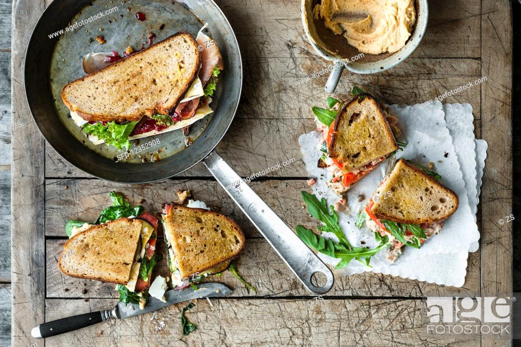 Stock Photo: Grilled sandwiches: cranberry, ham, and soft cheese, vitello tonnato with tuna and rocket, and aubergine, houmous, and feta.