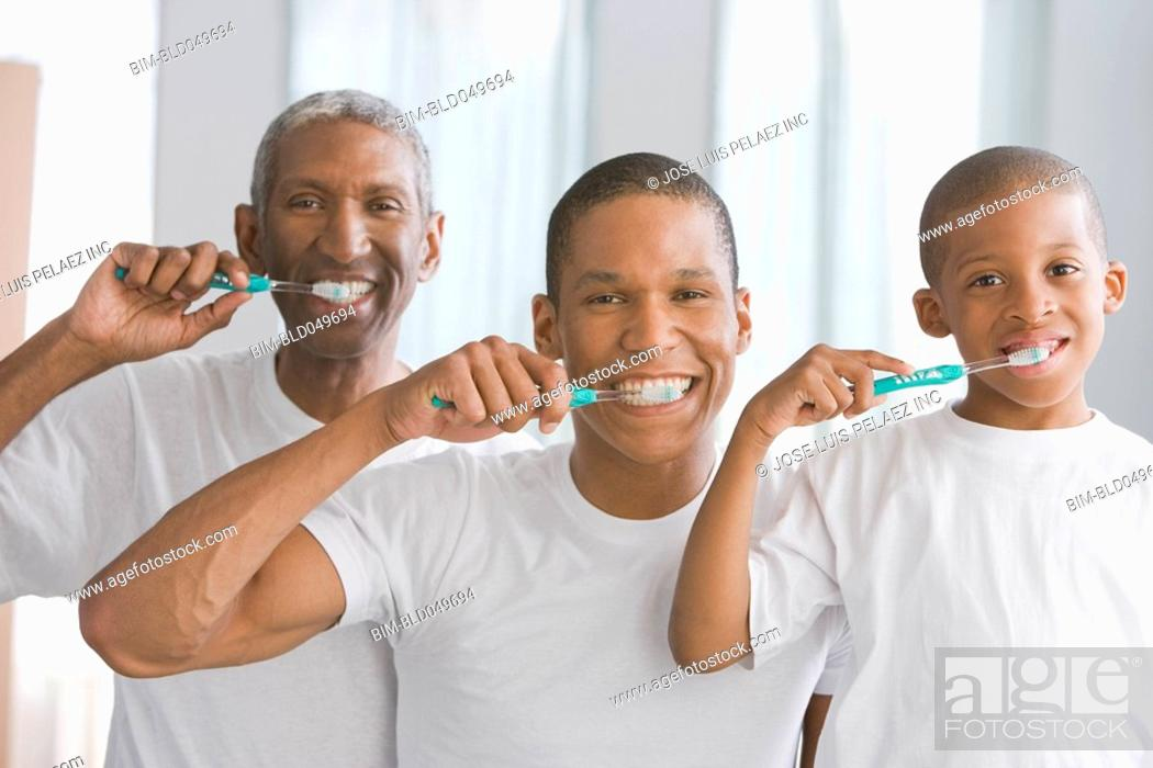 Stock Photo: African American grandfather, father and son brushing teeth.