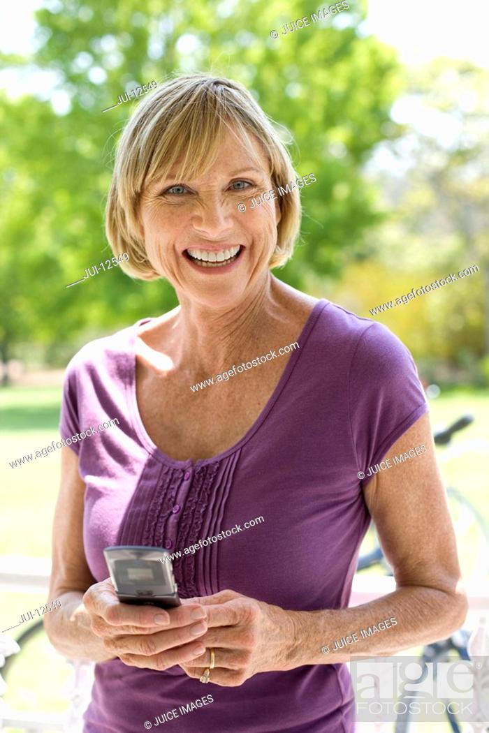 Stock Photo: Mature woman with mobile phone, bicycle in background, smiling, portrait.