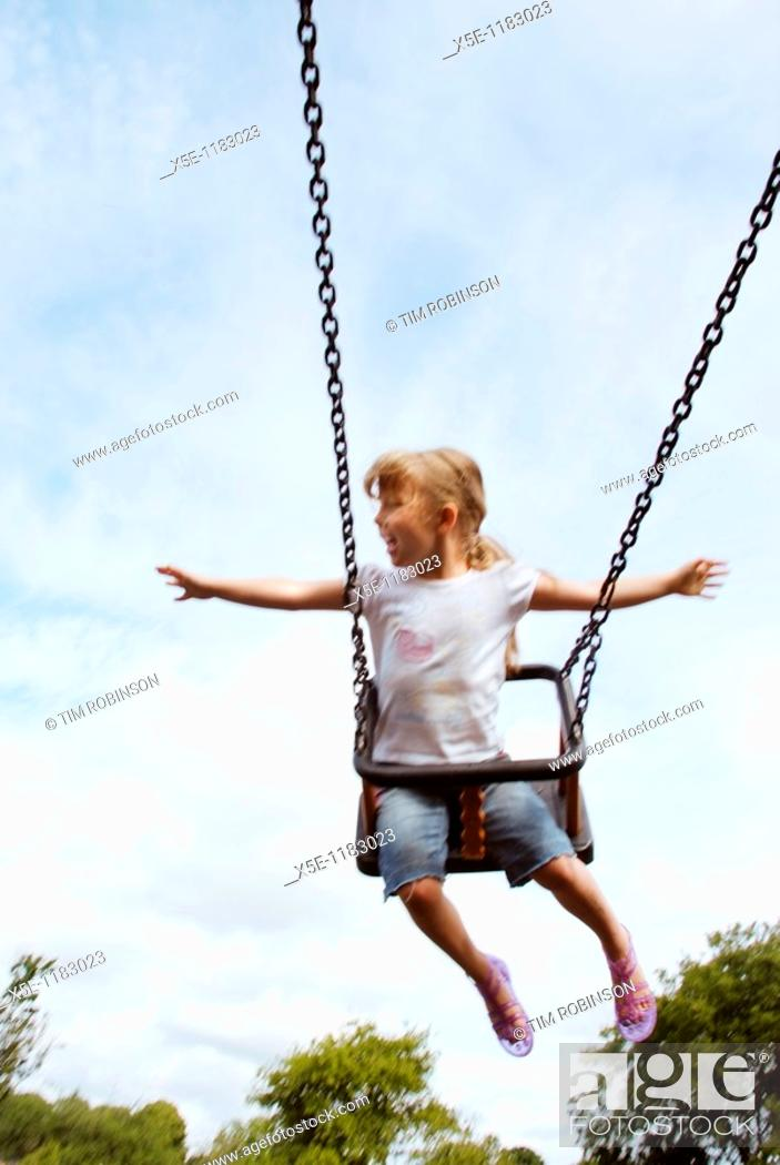 Stock Photo: Frontview 6 year girl riding high on swing in childrens playground, arms outstretched.