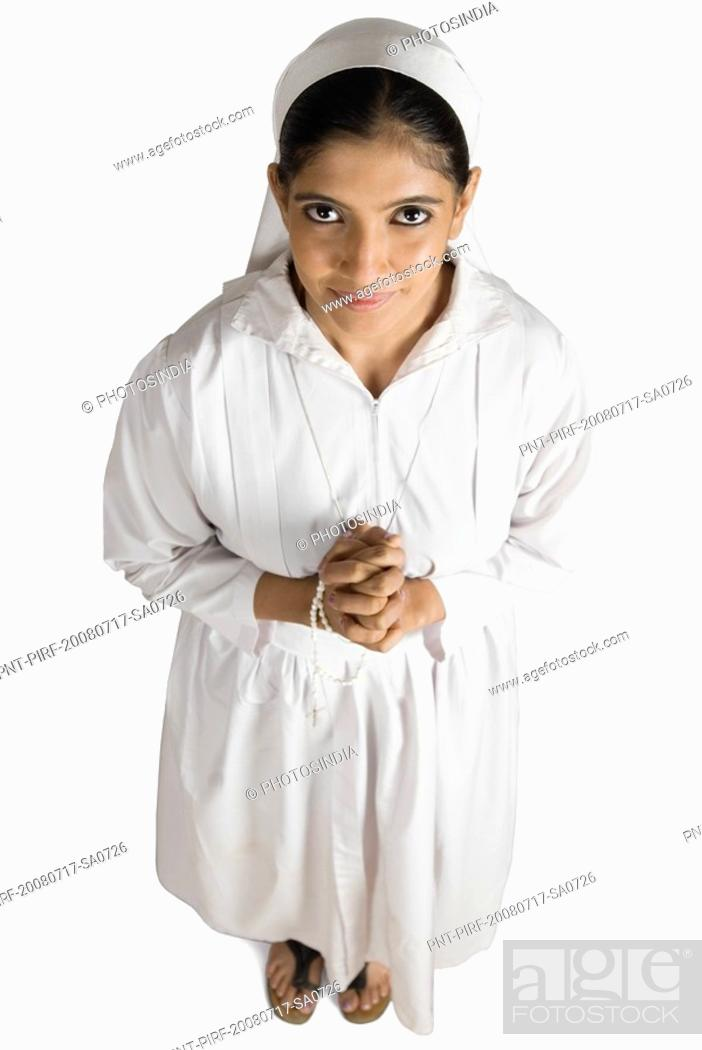 Stock Photo: Portrait of a nun standing in a prayer position.