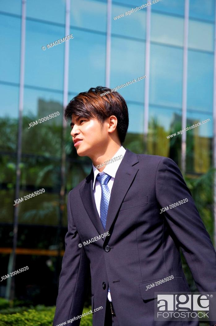 Stock Photo: Young man walking and looking away.