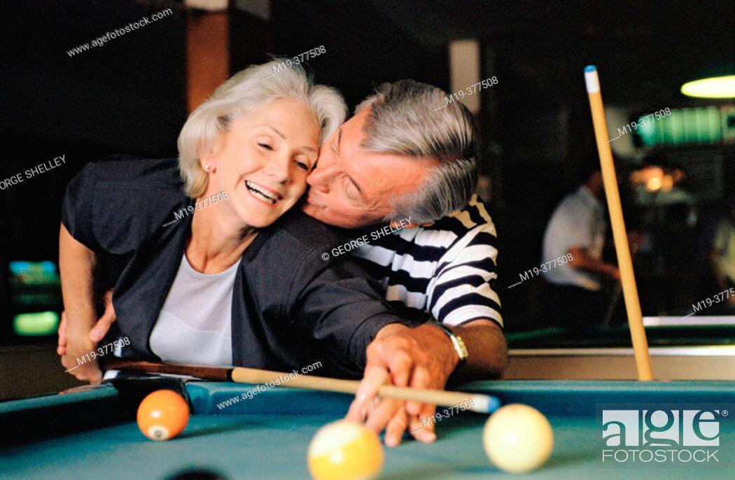Stock Photo: senior couple shooting pool.