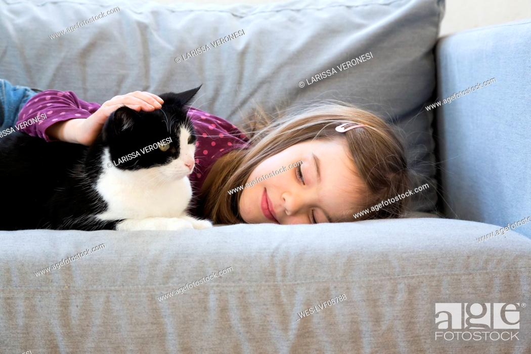 Stock Photo: Little girl lying on couch stroking cat.