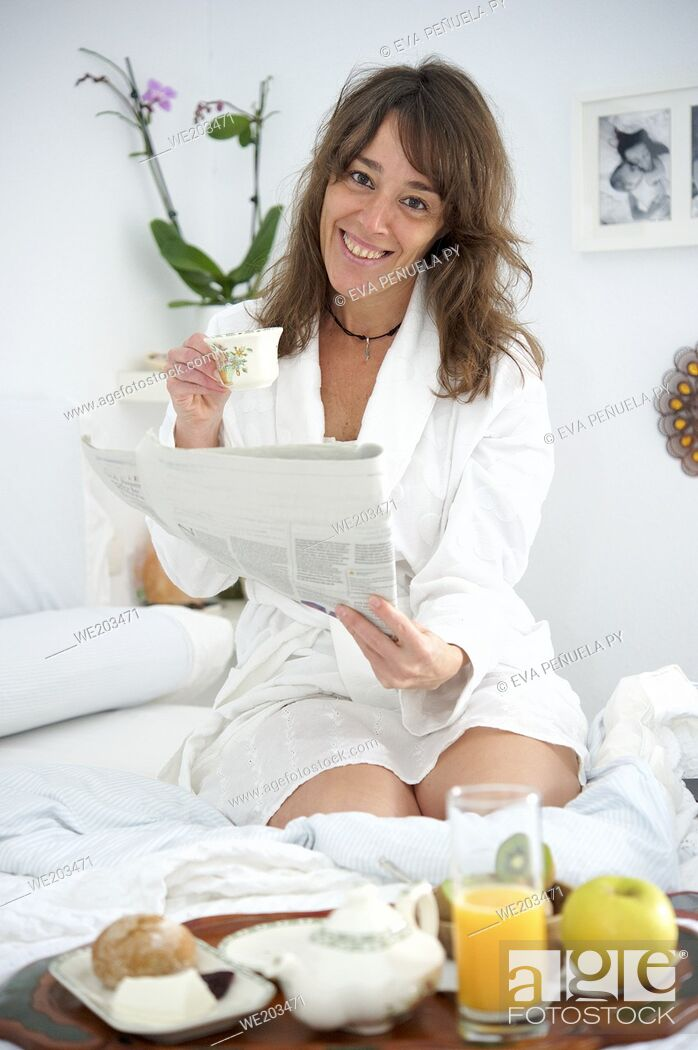 Imagen: Woman having breakfast in bed and reading a newspaper.
