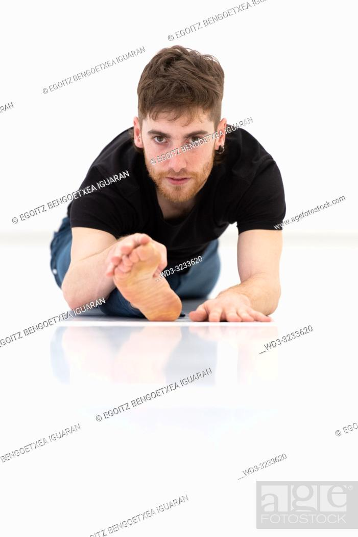 Stock Photo: Casual dressed young adult man stretching on white background.