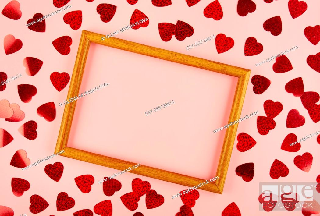 Stock Photo: Flat lay view at wooden frame among heart shaped tinsel on pink background.