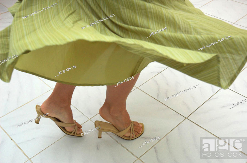 Stock Photo: Young woman's legs in a dance motion on tile floor.
