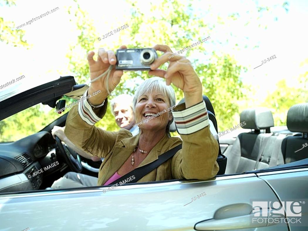Stock Photo: Senior couple driving in convertible car along country road, woman taking photograph, side view.