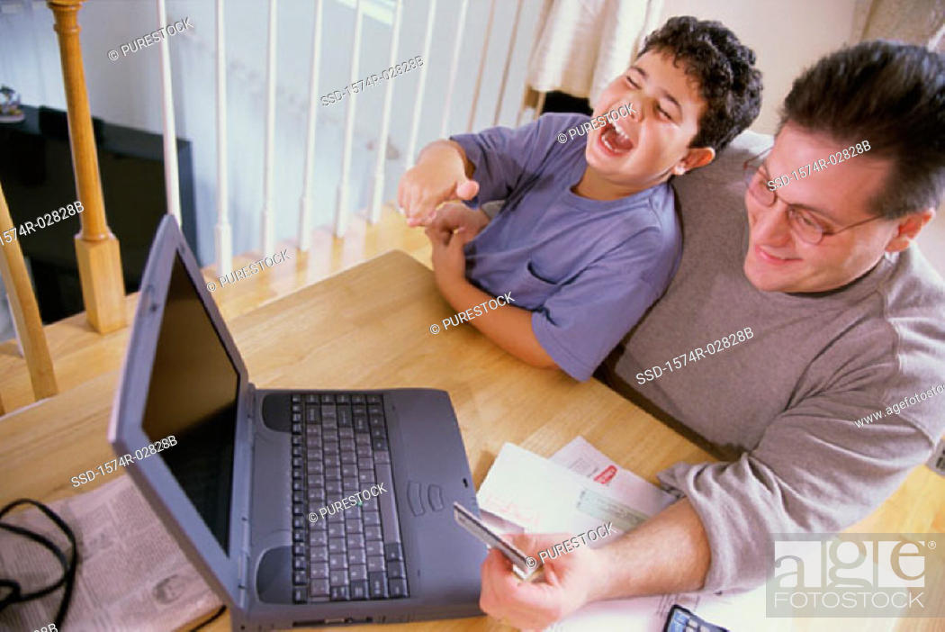 Stock Photo: High angle view of a father and his son sitting in front of a laptop holding a credit card.