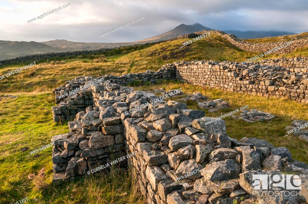 Stock Photo: Sunset view of the Hardknott Roman Fort in the English Lake District and the Scafell Mountain Range in the background.