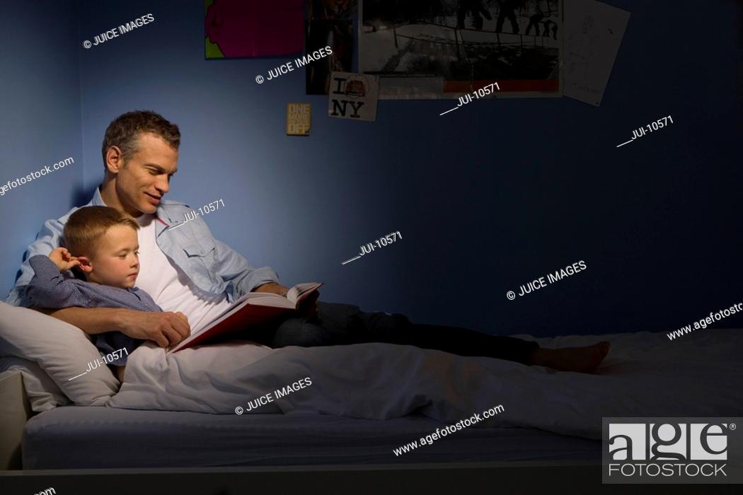 Stock Photo: Father reading to son 4-6 in bed, side view spot lit.