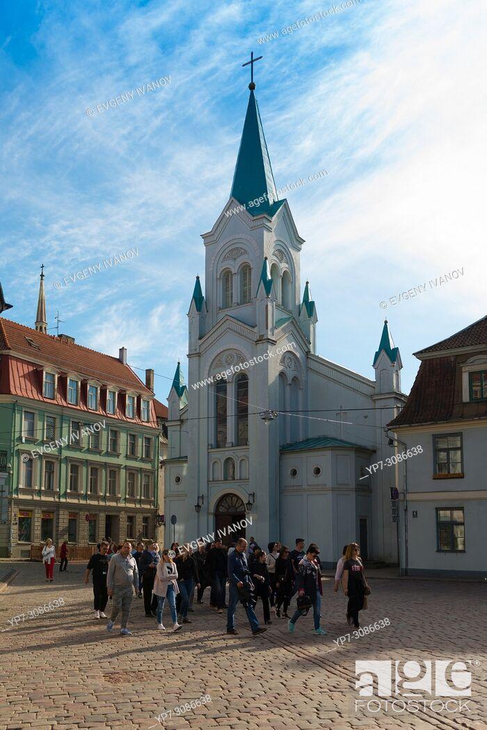 Stock Photo: Tourist group near Our Lady of Sorrows Church, Riga, Latvia.