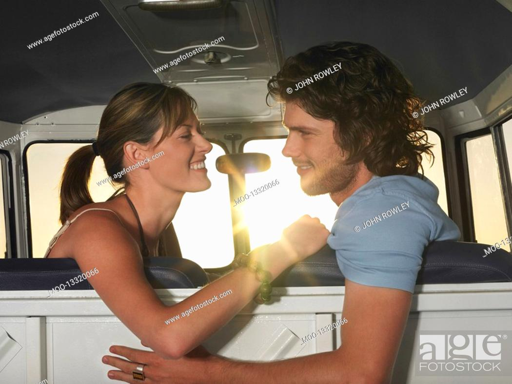 Stock Photo: Young couple face to face in front seat of van.