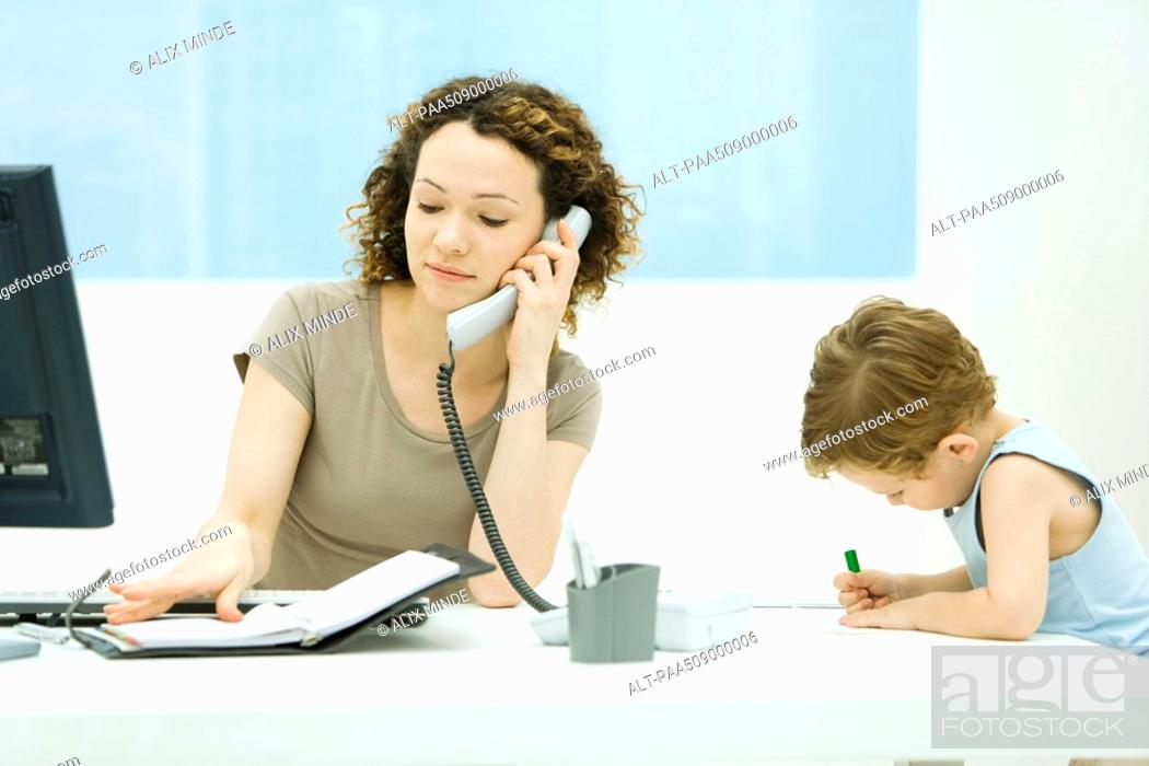 Stock Photo: Woman using phone and looking at agenda, young son sitting beside her, coloring.