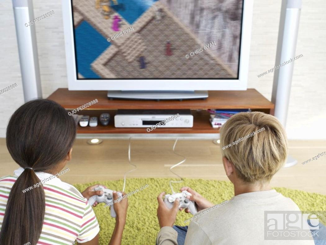 Stock Photo: Two young kids playing video games.