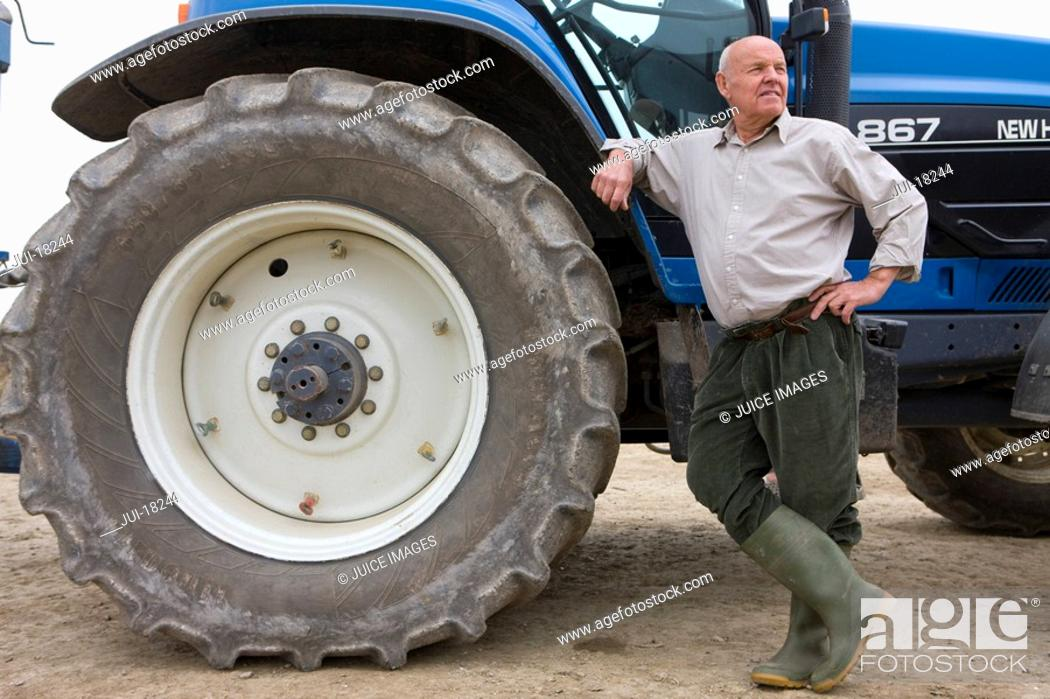 Stock Photo: Farmer leaning on tractor.