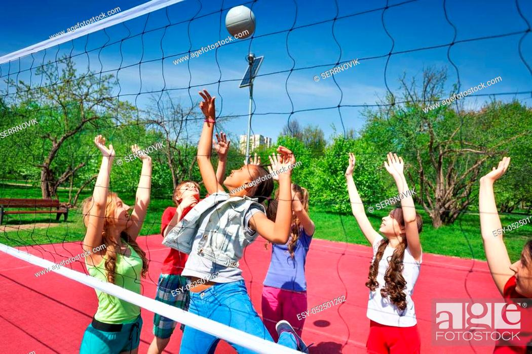 Stock Photo: View through volleyball net of playing teens trying to catch the ball on the playground during summer sunny day.